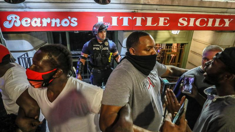 'They saved me': How protesters protected a lone cop, a moment captured in powerful photos