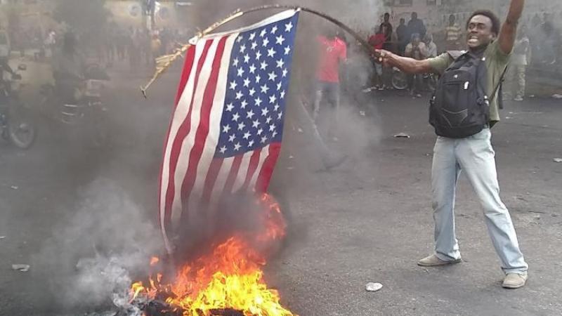 """Des manifestants crient """"vive Poutine"""" et brûlent un drapeau américain"""